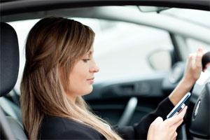 Frau mit Handy am Steuer