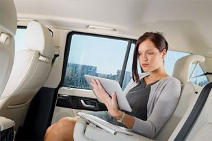 Frau mit Tablet im Auto