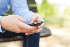 mann-mit-smartphone-auf-bank