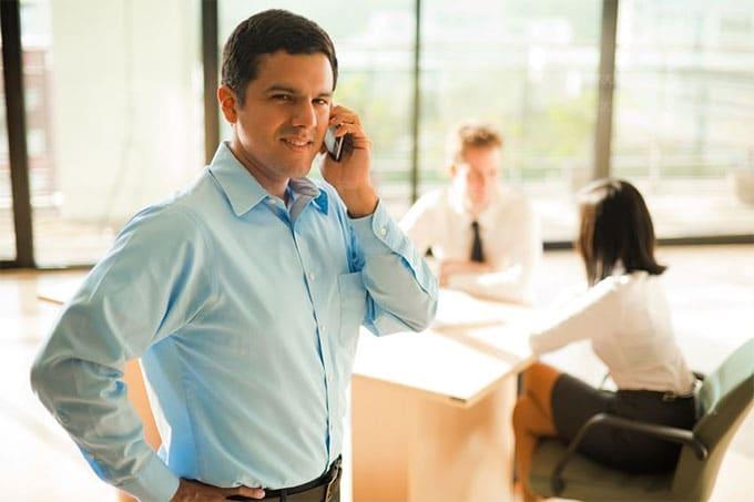 Mann mit Smartphone im Büro
