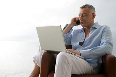 Mann mit Telefon un Laptop